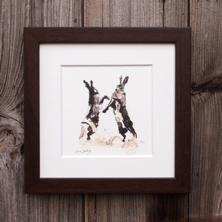 Ink painting of two boxing hares.